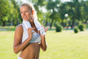 young attractive woman with a white towel around his neck, resting after sport exercises